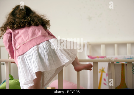 little girl jumping inside the bed - Stock Photo