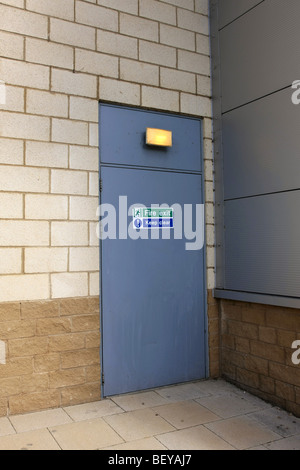 Fire exit door at the back of a building - Stock Photo