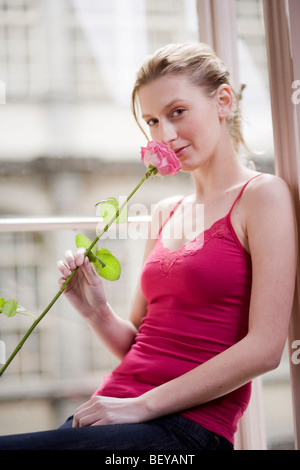 Young Woman Sitting in Window and Holding Flower - Stock Photo