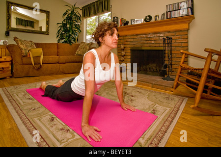 A 50-year-old woman exercises on a mat in her Mission Viejo, California, living room. - Stock Photo