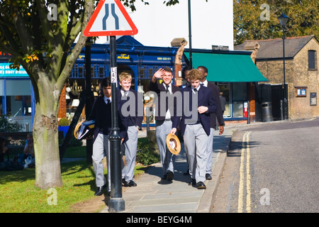 Harrow on the Hill , Harrow School pupils students in uniform walking in high street with traditional straw boaters - Stock Photo