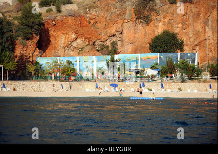 People sunbathing on one of the small beach areas in the bay of kalkan - Stock Photo