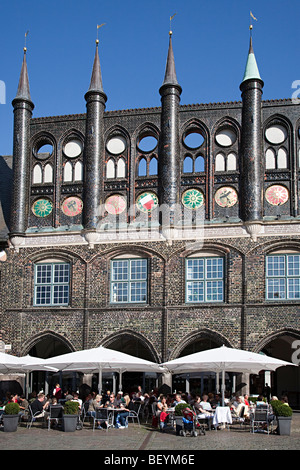 People sitting eating at cafe bar in market square outside the Town Hall Lubeck Germany - Stock Photo