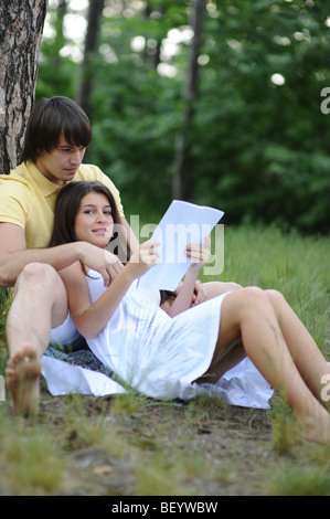 Young Couple Sitting under a Tree Reading - Stock Photo