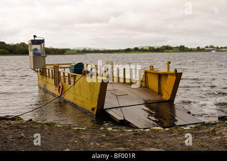 Small car ferry with ramp lowered on a lake - Stock Photo