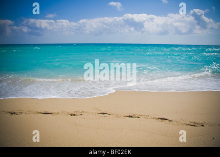Footprints in sand and stunning blue ocean at Miami beach. South beach Miami Florida USA - Stock Photo