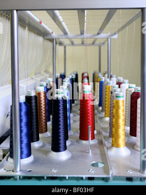 Threads in a rainbow of colors are wound onto special bobbins for use on industrial embroidery machines. - Stock Photo