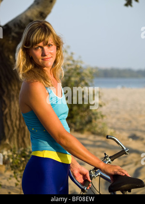Young female blond cyclist staying looking to camera smiling - Stock Photo