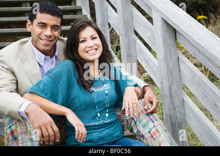 Couple sitting on a staircase and smiling - Stock Photo