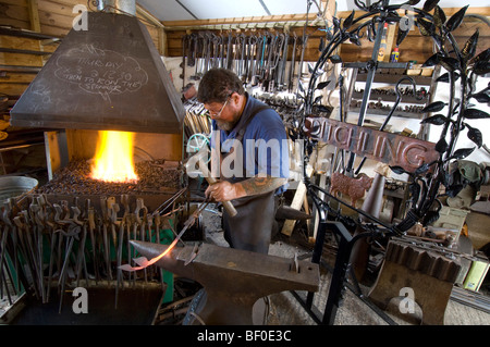 A village blacksmith forging a new sign for Ditchling in Sussex, using the famous London Underground Johnston typeface. - Stock Photo