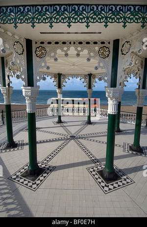 The restored Brighton bandstand on the seafront with a Brighton and Hove Bus & Coach Company bus passing behind - Stock Photo