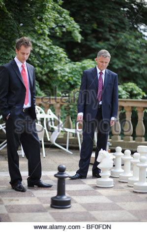 Two Businessmen Playing Giant Chess - Stock Photo
