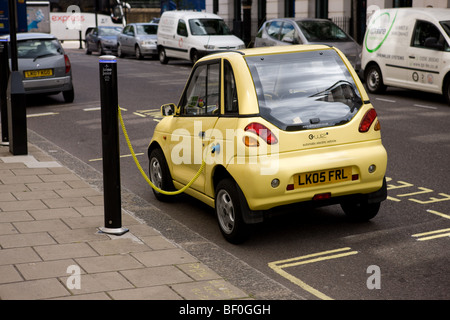 An Electric Car charges up at one of Westminster's 'Juice Point'  parking bays - Stock Photo