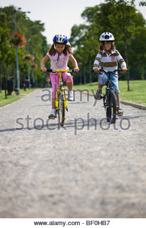 Little boy and girl riding bycicles - Stock Photo