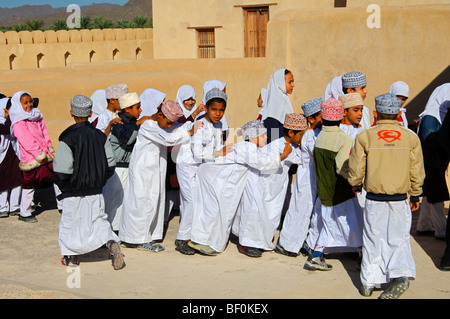 Female teacher of a mixed school class of lively boys and girls on an excursion in the Castle of Nizwa, Sultanate - Stock Photo
