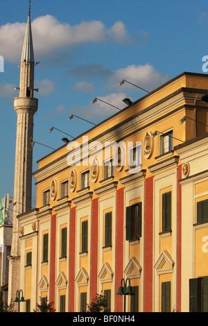 Minaret of the Etham Bey Mosque & facade of government buildings at Skanderbeg Square in Tirana, Albania - Stock Photo