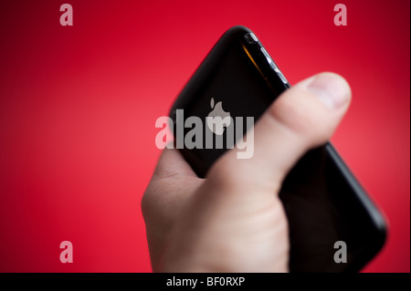 A black Apple iPhone 3G hand held in front of a red background. - Stock Photo