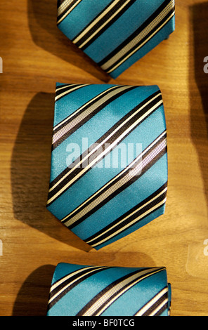 A row of folded silk ties for sale in a menswear store. - Stock Photo