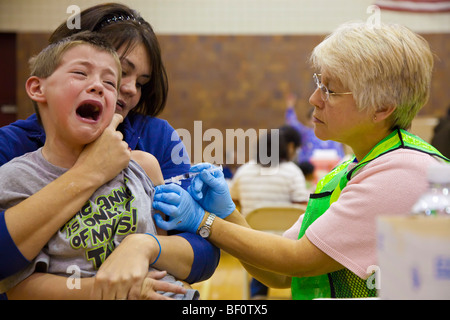 Hamtramck, Michigan - A health care worker vaccinates a boy against the H1N1 swine flu. - Stock Photo