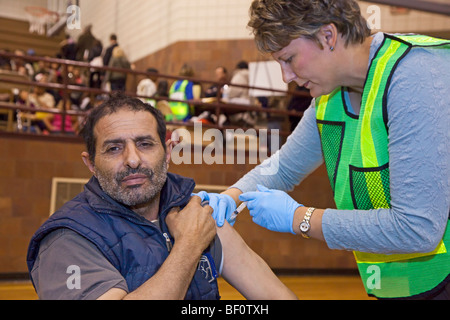 Hamtramck, Michigan - A health care worker vaccinates a man against the H1N1 swine flu. - Stock Photo