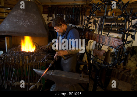 A village blacksmith forging a new sign for Ditchling in Sussex - Stock Photo