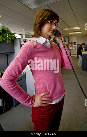 A young woman talks on the phone at a financial consultant's office in Irvine, California. - Stock Photo