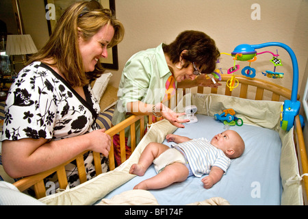 Babysitting her 6-month-old grandson, a grandmother in Laguna Niguel, California, interacts with the child as a - Stock Photo