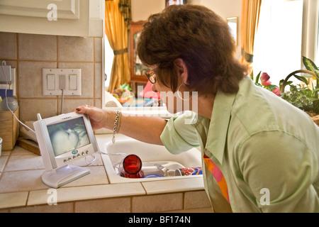 Babysitting her 6-month-old grandson, a grandmother in Laguna Niguel, California, checks her 'nannycam' TV - Stock Photo