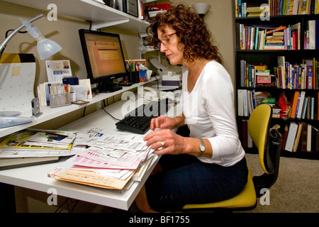 A 50-year-old self-employed woman works in her home office in Mission Viejo, California. - Stock Photo