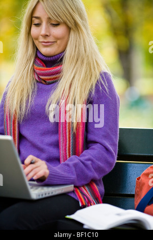 A woman sitting on bench in a park using a laptop, Stockholm, Sweden. - Stock Photo