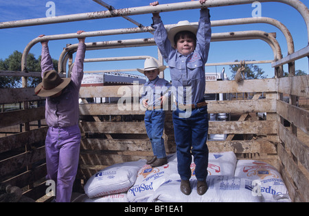 Boys + girl, children, cowboys matching Stetson hats, shirts and jeans, play in back of truck during rodeo, Queensland - Stock Photo