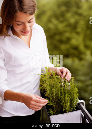Young woman pottering about on her balcony, Sweden. - Stock Photo