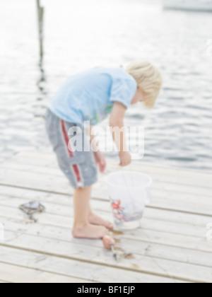 Scandinavian boy on a jetty, Sweden. - Stock Photo