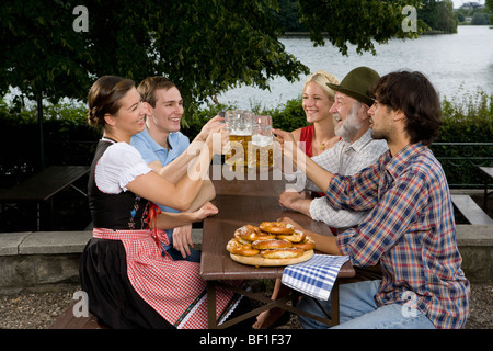 Five people in a beer garden toasting glasses - Stock Photo