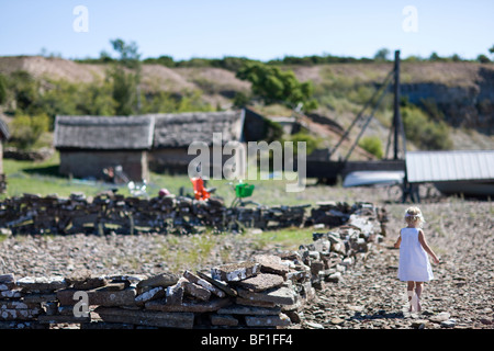 A little girl in an old fishing port, Sweden. - Stock Photo