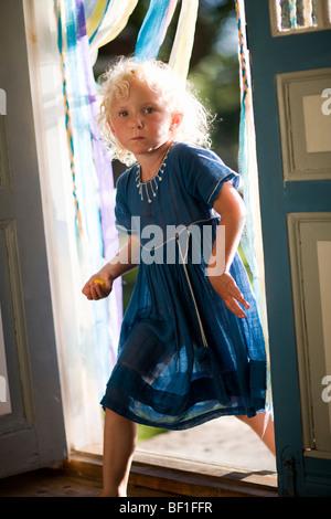 A Scandinavian girl passing through a doorway, Sweden. - Stock Photo