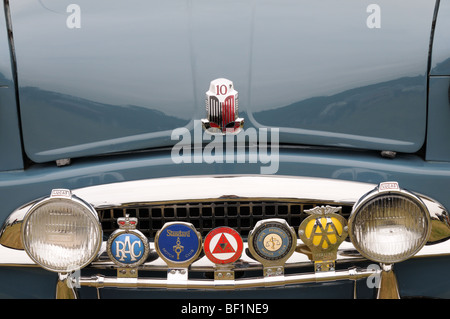 A Collection of Car Badges on the Grill of a Triumph Standard 10 classic car - Stock Photo