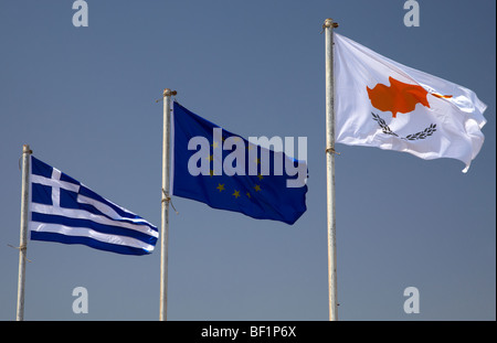 greek republic of cyprus and eu flags flying in a blue sky in cyprus - Stock Photo