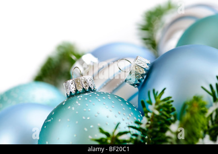 Many Christmas decorations laying in pine branches - Stock Photo