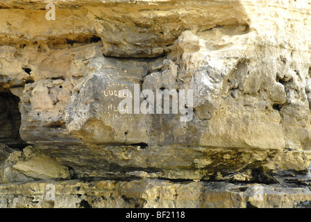Writing carved in the stone on a beautiful rocky beach on Falesia beach in the Algarve in Portugal. - Stock Photo