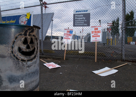 Boeing Machinists Union 'On Strike' picket signs found at an unmanned post.  A Jack-o-lantern decorates an oil can - Stock Photo
