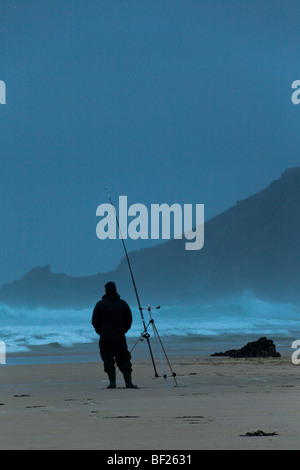 A fisherman beachcasting with a rod. Cornwall England - Stock Photo