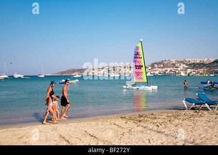 Family walking along the beach, Mellieha Bay, Malta, Europe - Stock Photo