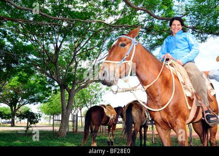 Woman prepares for a horseback ride at Rio da Prata ecological reserve, Bonito, Mato Grosso do Sul, Brazil - Stock Photo