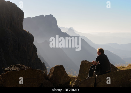 Hiker looking out toward South Peak from Twin's Cave in the Drakensberg Ukhahlamba National Park, Kwazulu Natal, - Stock Photo