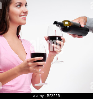 Person's hand pouring wine into a glass held by a woman - Stock Photo