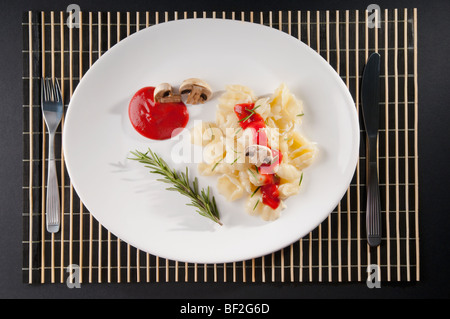 Rosemary garnish on conchiglie pasta with mushrooms - Stock Photo