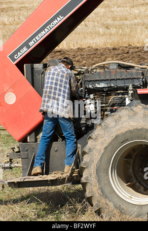 A farmer performs maintenance on a tractor in the field during planting season / near Pullman, Palouse Region, Washington, - Stock Photo