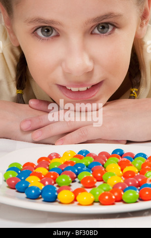 Portrait of a girl with a plate of candy - Stock Photo