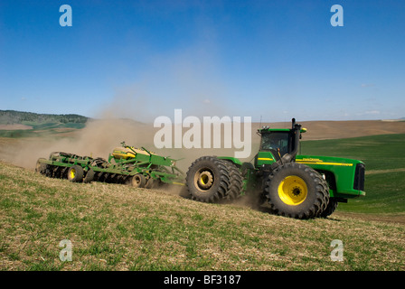 A tractor and air seeder replant areas of winter wheat damaged by lingering snow packs in the rolling hills of the - Stock Photo